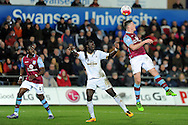 Aston Villa's Ciaran Clark (r) wins a header from Swansea's Bafetimbi Gomis. Barclays Premier league match, Swansea city v Aston Villa at the Liberty Stadium in Swansea, South Wales on Saturday 19th March 2016.<br /> pic by  Carl Robertson, Andrew Orchard sports photography.