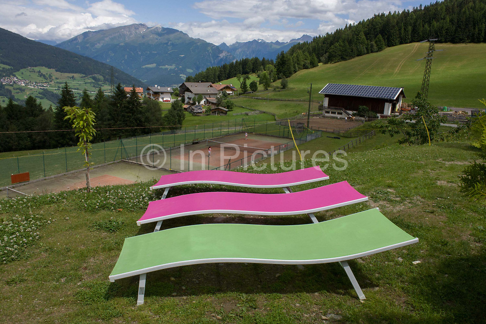 Vacant sun loungers at a health spa on the Jaufenpass, Dolomites, South Tyrol, Italy. Lioned up as a threesome, the loungers are empty, vibrant colour against a background of green valleys and darker mountains. The Jaufenpass (Italian: Passo di Monte Giovo) (alt 2094m.) is a high mountain pass in the Alps in the South Tyrol in Italy. It connects Meran and Sterzing on the road to the Brenner Pass. It is the northernmost pass in the Alps that is completely in Italy. The pass road is very winding, with many switchbacks.