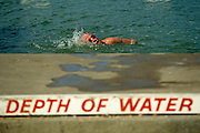 A male swimmer performs the Crawl across this scene of frewsh water bathing in the Serpentine Lake in London's Hyde Park. As the man twists his head to gulp in air, breathing a lungful of oxygen, he passes the lettering stencilled on the poolside warning of shallow water. This bathing area is where the normally busy Serpentine Swimming Club has the use of this Royal Lake known as Lansbury's Lido. It is now normally open only in the summer, but one traditional event occurs each year on New Year's Day, when the ice is broken and brave bathers dive into the cold waters of the lake. The Serpentine will be used for the swimming leg of the triathlon at the London 2012 Olympics. The pool was formed in 1730, its name from a snakelike, curve. Queen Caroline wife of George II ordered the damming of the River Westbourne and other natural ponds in Hyde Park...