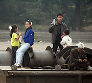 A young man holds what appears to be a gun as he stands on the Sunuiju pier on the Sino-North Korean border October 10, 2006.  DPRK, north korea, china, dandong, border, liaoning, democratic, people's, rebiblic, of, korea, nuclear, test, rice, japan, arms, race, weapons, stalinist, communist, kin jong il