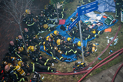 © Licensed to London News Pictures. 14/06/2017. London, UK. A large group of firefighters rest at the scene of a huge fire at Grenfell tower block in White City, London. The blaze engulfed the 27-storey building with 200 firefighters attending the scene. There were reports of people trapped in the building. Photo credit: Guilhem Baker/LNP