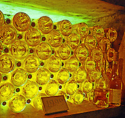 The Oremus winery in Tolcsva, Tokaj: bottles lying in the underground cellar, backlit, giving a wonderful, magical golden-reddish glow. Waiting to mature. 1999 carved in stone, 5 puttonyos Aszu. Oremus is owned by the Alvarez family that also owns Vega Sicilia in Spain It is managed by Andras Bacso. Credit Per Karlsson BKWine.com
