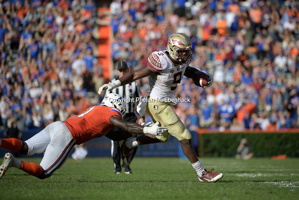 Florida State running back Jacques Patrick (9) rushes for yardage in front of Florida linebacker Vosean Joseph (11) during the second half of an NCAA college football game Saturday, Nov. 25, 2017, in Gainesville, Fla. FSU won 38-22. (Photo by Phelan M. Ebenhack)