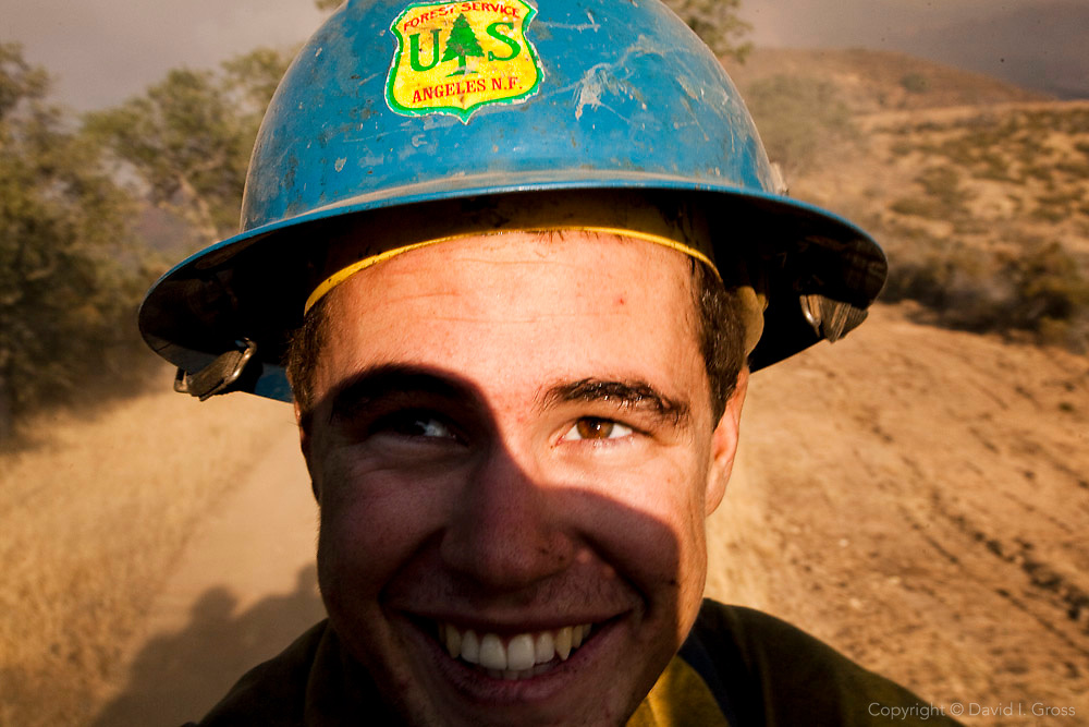 """Travis """"Kid"""" Calka of the Texas Canyon.Hotshots hangs on to the back of a truck carrying the rest of his crew at the La Brea Fire as they rush along a fire break to put out a spot fire ."""