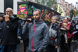 London, UK. 12 October, 2019. Climate activists from Extinction Rebellion bearing a coffin featuring the images of extinct animals take part in the XR March from Marble Arch to Russell Square on the sixth day of International Rebellion protests to demand a government declaration of a climate and ecological emergency, a commitment to halting biodiversity loss and net zero carbon emissions by 2025 and for the government to create and be led by the decisions of a Citizens' Assembly on climate and ecological justice. Credit: Mark Kerrison/Alamy Live News
