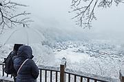 Two people on balcony looking at scenic winter landscape, Shirakawa-go, Japan
