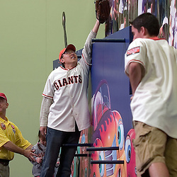 """Fans pose for photographs while making """"home-run saving catches"""" during the 2007 DHL All-Star FanFest, Saturday, July 7 at Moscone Center West in San Francisco...Photo by David Calvert/MLB.com"""