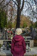 A woman remembers her deceased loved ones at Rakowicki Cemetery in Krakow, Poland in 2019.