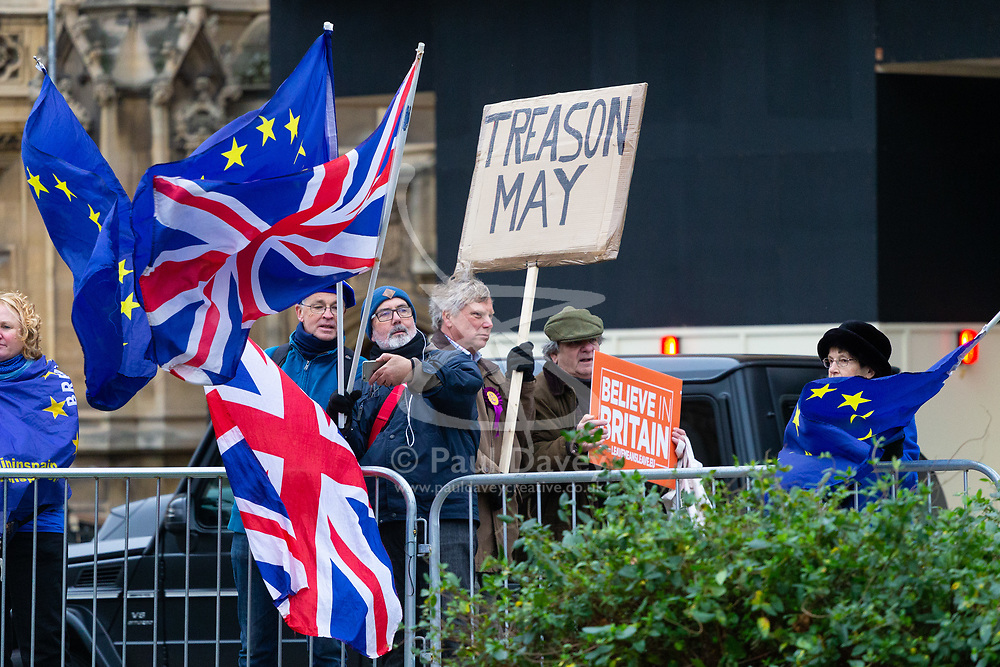 """Leave and remain protesters are seen outside Westminster Palace, with one protester wearing a UKIP badge holding a placard that says """"Treason May"""". London, January 07 2019."""