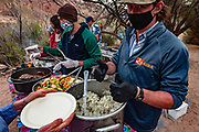Dinner served at Lava Canyon Camp at Colorado River Mile 66. Day 4 of 16 days boating 226 miles down the Colorado River in Grand Canyon National Park, Arizona, USA. Masks were required during the initial meeting in Flagstaff, for bus rides, for initial embarkation at Lees Ferry, when being served for all meals, and for final disembarkation at Diamond Creek. Otherwise, this relatively safe outdoor activity was unencumbered by facial coverings, April 3-18, 2021.