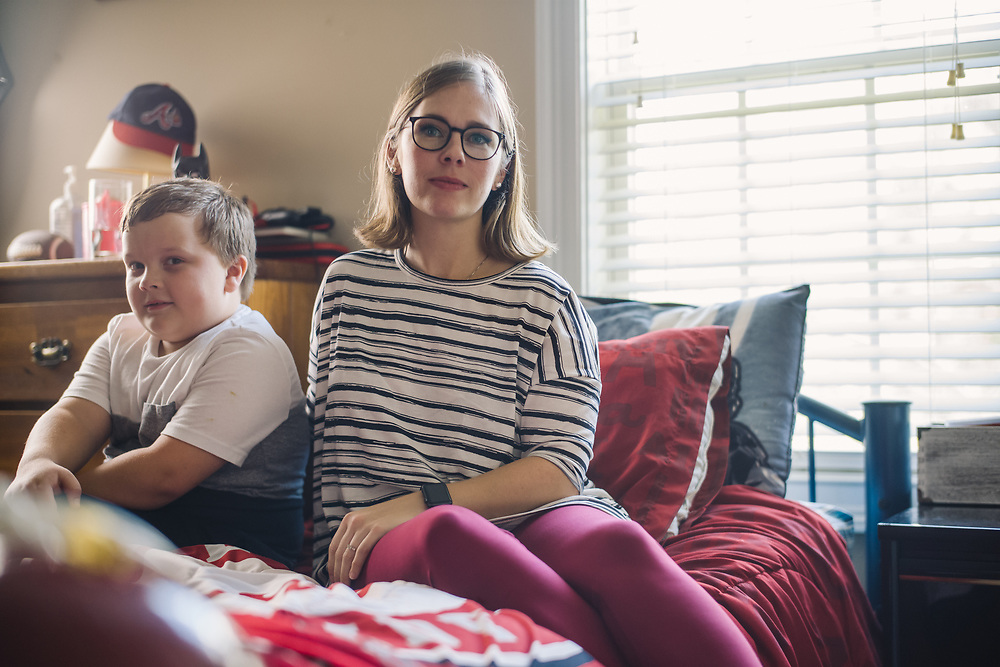 """GUNTERSVILLE, AL – SEPTEMBER 3, 2019: Brianna Barker, 34, sits with her 8 year-old son, Callen, in his bedroom. As the founder of Huntsville's chapter of the International Cesarean Awareness Network (ICAN), Barker facilitates support meetings and moderates online forums on topics surrounding cesarean birth in an effort to support mothers seeking a vaginal birth after cesarean (VBAC). <br /> <br /> Barker's first child was born prematurely by cesarean. Reflecting on the birth of Callen, her second child, Barker recalls feeling alone in her effort to have a normal vaginal birth. """"It was really hard. I didn't have a doula or any support network. Even today I have recurring nightmares where I'm alone in a dark hospital in labor. In my subconscious, I was just so alone."""" With their third and fourth children the Barkers chose an out of hospital birth experience – driving 2 ½ hours to Tennessee for every prenatal appointment. During this time, Barker was involved in the fight to legalize midwifery in Alabama. """"I knew I had many privileges that many others didn't have. So I went to Montgomery. And the other mom's and I – we all have this collective PTSD from dragging our screaming babies around Montgomery, marching to hearings and all that, just so there would be accountability. It's incredible the amount of barriers to access for v-backs, but I was able to have a vaginal birth with Callen, and for that I'm so grateful."""" <br /> <br /> Although midwifery has been legalized in Alabama, from Barker's perspective """"the fight is not really over."""" Today, many hospitals still ban vaginal births after cesarean. """"There's just so much misinformation, even about what the guidelines are,"""" Barker says. """"They're essentially mandating surgery for a large percentage of their patients, and I don't want that for other people. I want to make a difference, so other mom's can have the same experience I had. And if enough moms and families come together with more inform"""