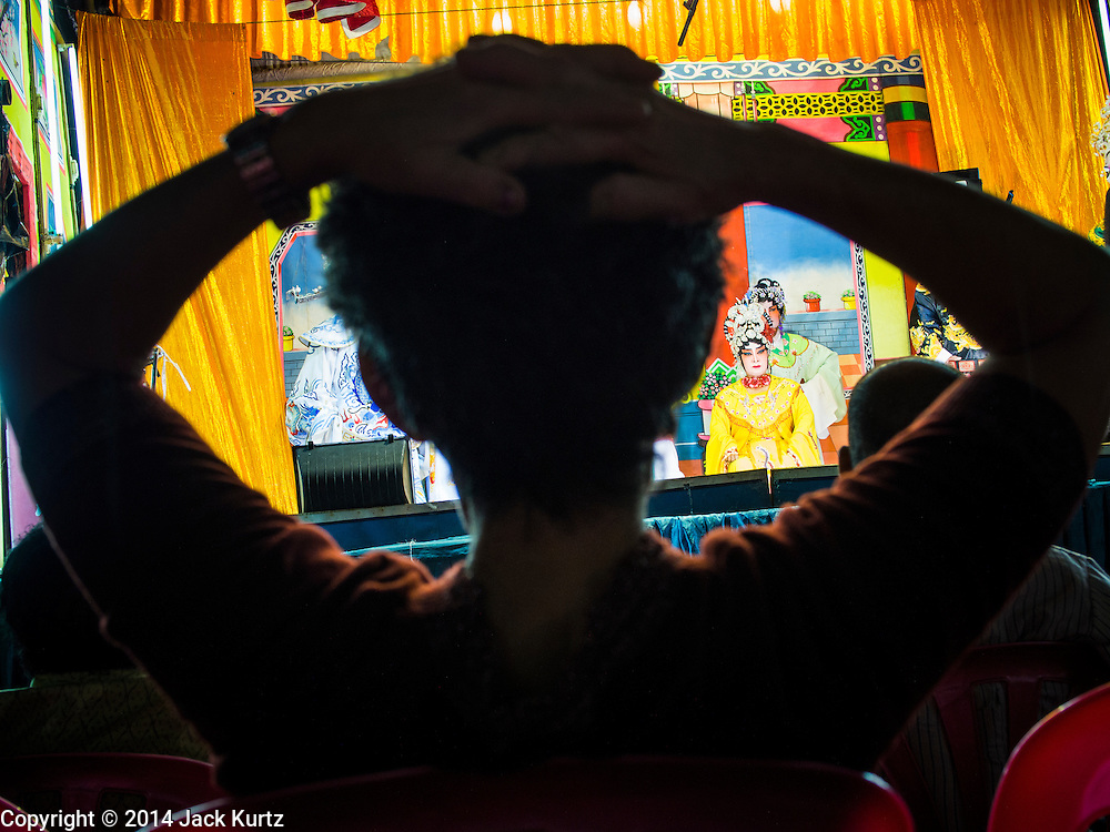 """18 AUGUST 2014 - BANGKOK, THAILAND:      A member of the audience relaxes while she watches the Lehigh Leng Kaitoung Opera troupe perform during a performance at Chaomae Thapthim Shrine, a small Chinese shrine in a working class neighborhood of Bangkok. The performance was for Ghost Month. Chinese opera was once very popular in Thailand, where it is called """"Ngiew."""" It is usually performed in the Teochew language. Millions of Chinese emigrated to Thailand (then Siam) in the 18th and 19th centuries and brought their culture with them. Recently the popularity of ngiew has faded as people turn to performances of opera on DVD or movies. There are still as many 30 Chinese opera troupes left in Bangkok and its environs. They are especially busy during Chinese New Year and Chinese holiday when they travel from Chinese temple to Chinese temple performing on stages they put up in streets near the temple, sometimes sleeping on hammocks they sling under their stage. Most of the Chinese operas from Bangkok travel to Malaysia for Ghost Month, leaving just a few to perform in Bangkok.   PHOTO BY JACK KURTZ"""