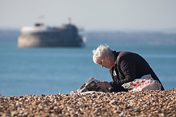 © Licensed to London News Pictures. 27/10/2017. Portsmouth, UK.  A woman reading the newspaper and enjoying the sunny autumn weather on Southsea beach today, 27th October 2017.  Photo credit: Rob Arnold/LNP