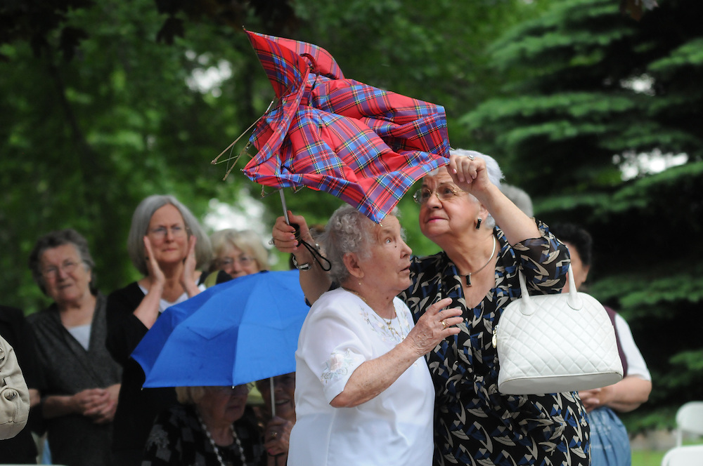 Lucjana Wilczewska (r to l) and Anna Wolkowska manage an umbrella mangled by the winds of an approaching storm during a Memorial Day Field Mass celebrated at St. Adalbert Cemetery in Niles.