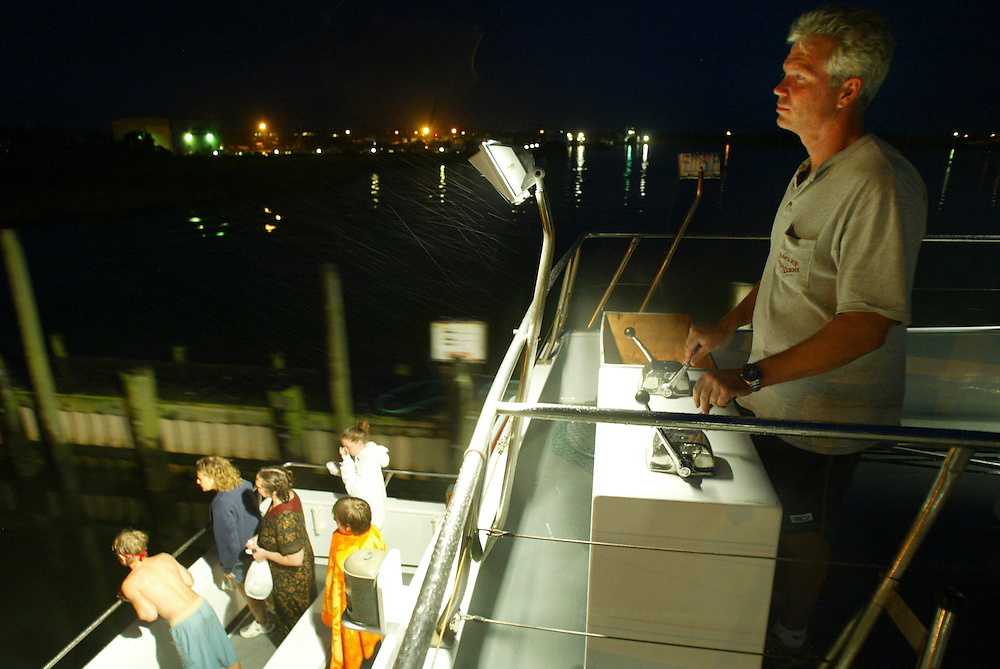 (DAYIN) Barnegat 8/7/1002 Miss LBI's captain Ken Nutt backs his boat in to the dock as patrons of his sunset cruise stand in the stern of the boat.  Michael J. Treola Staff Photographer....MJT