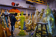 Workshop with man spraying Buddhist figures and statues. Situated in the heart of Bangkok, near the famous Golden swing, is a series of streets and alleyways dedicated to the manufacture of Buddhist and Hindu icons together with other religious paraphernalia.
