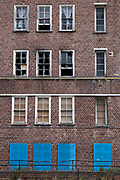 The boarded up windows of a block of empty and fire damaged council flats in Hackney, London, United Kingdom.  Empty, abandoned or derelict council houses are also known as 'voids'.
