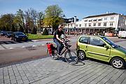 In Zeist wordt een man met een dochtertje voorop de fiets krap ingehaald door een auto.<br /> <br /> A car is passing a man with a child on front of the bike in the city center of Zeist.
