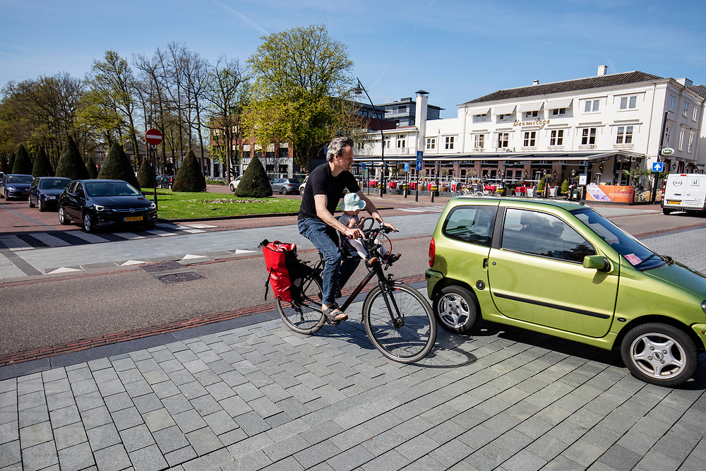 In Zeist wordt een man met een dochtertje voorop de fiets krap ingehaald door een auto.<br /> <br /> A car is passing a man with a child on front of the bike in the city center of Zeist.