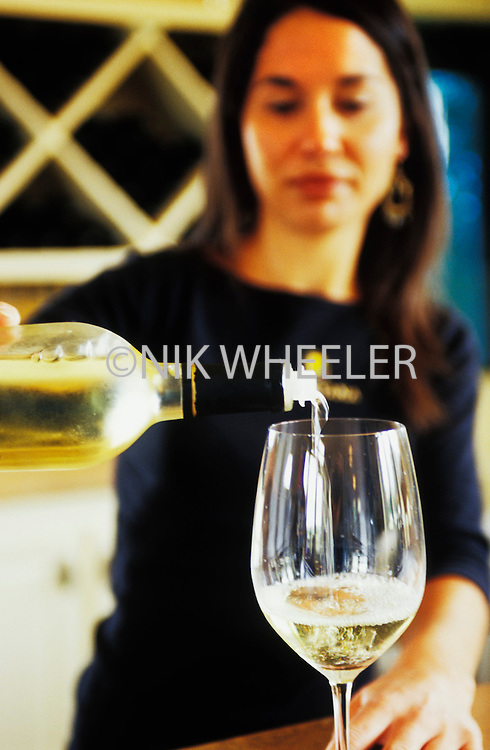 Woman pours Wine at wine tasting at winery in Edna Valley in San Luis Obispo County , California.