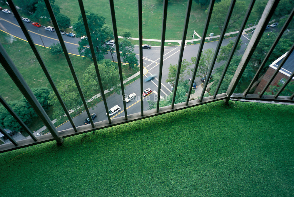 Looking down a balcony with iron railing and faux grass