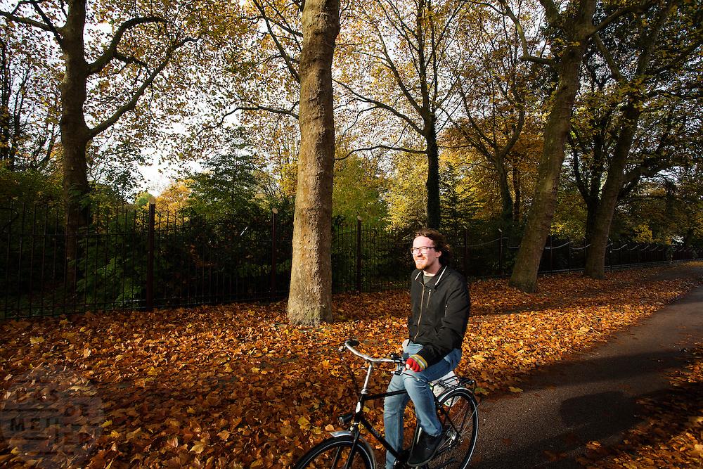 In Utrecht rijden fietsers langs het Julianapark waar de bomen mooie herfstkleuren hebben.<br /> <br /> In Utrecht cyclists pass the Juliana park with trees in autumn colors.