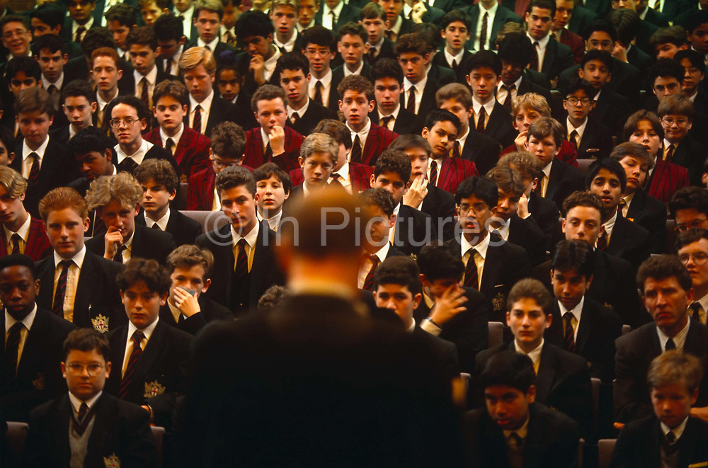Looking down from a high vantage point, we se boy pupils seated as they gather in front of the Headmaster during morning assembly at the City of London School for boys in central London. Individual faces in neat rows stretch into the distance as we look past the Headmaster who is addressing, facing his students. Some seem serious, a few are looking bored while one boy can be seen coughing into his hand and another looking away with a smirk.  We can see a diverse range of ethnic backgrounds, skin colours and hairstyles. The City of London School (CLS) is a boys' public school on the banks of the River Thames. It traces its origins to a bequest of land by John Carpenter, town clerk of London in 1442. The City of London has a resident population of under 10,000 but a daily working population of 311,000. The City of London is a geographically-small City within Greater London, England. The City as it is known, is the historic core of London from which, along with Westminster, the modern conurbation grew. The City's boundaries have remained constant since the Middle Ages but  it is now only a tiny part of Greater London. The City of London is a major financial centre, often referred to as just the City or as the Square Mile, as it is approximately one square mile (2.6 km) in area. London Bridge's history stretches back to the first crossing over Roman Londinium, close to this site and subsequent wooden and stone bridges have helped modern London become a financial success.