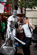 Tourist jokes as a sword is held to him by a street performer dressed as a gladiator. Covent Garden in the West End of London.