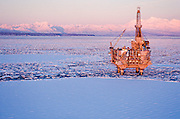 Alaska. Cook Inlet. Oil rig  production platform in the icy inlet with Mt Spurr in background.