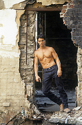 shirtless man in an abandoned building holding <br />