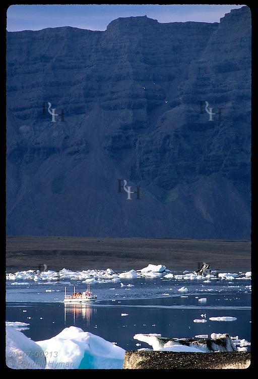 Amphibious boat glides by ice calved from Breidamerkurjokull glacier in Jokulsarlon (Glacier Lagoon) beneath towering rock face; Iceland.