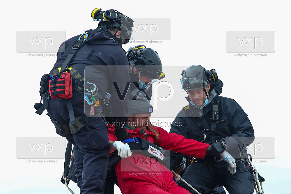 """Tamworth, United Kingdom, May 25, 2021: Police carry one of three arrested activists of the """"Palestine Action"""" activist group who scaled on the rooftop of an Israeli owned arms manufacturer Elbit on the early morning of Tuesday, May 25, 2021. Activists painted red colour on Building's roof as well as its logo """"Elite KL"""".  (Photo by Vudi Xhymshiti)"""