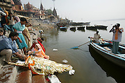 A relative splashes Ganges River water onto the face of Savitridevi Mishra at the cremation grounds of Jalasi Ghat.