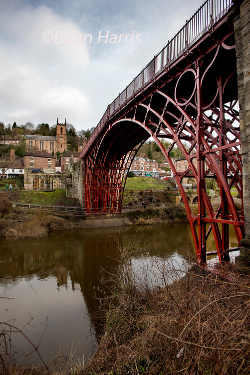 """Ironbridge, Shropshire, England UK. 26 January 2019<br /> Newly restored and repainted in original red colour following a £3.6million restoration the Iron Bridge at Ironbridge constructed by Abraham Darby III in 1779 and opened in 1781 crosses the River Severn and the Ironbridge Gorge. The site has been a designated UNESCO World Heritage Site since 1986.<br /> Iron Bridge was the first fully constructed Cast Iron Bridge in the World.The Iron Bridge is made of cast iron, which is not a good structural material for handling tension or bending moments because of its brittleness and relatively low tensile strength compared to steel and wrought iron.<br /> In January 2017 English Heritage announced a £1.2 million restoration project on the Iron Bridge, starting in September 2017, the """"biggest ever conservation project"""" undertaken by English Heritage. The cost was quoted in 2018 at £3.6 million, with English Heritage describing it as """"an ambitious conservation of its ribs and arches, its stonework and decking.""""In 2018 the bridge was also repainted in a dark red colour, now thought to represent the original paintwork of the bridge when first constructed."""