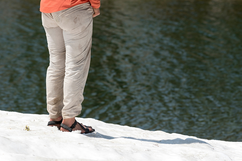 Woman wearing sandles standing on snowfield next to a lake in Oregon's Wallowa Mountains.