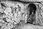 A black and white portrait of a Moran warrior of the Maasai tribe sitting in the doorway of a hut in his village ,Amboseli, Kenya, Africa