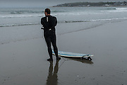 A surfer in a wetsuit with his surfboard on the beach at Narragansett, Rhode Island.