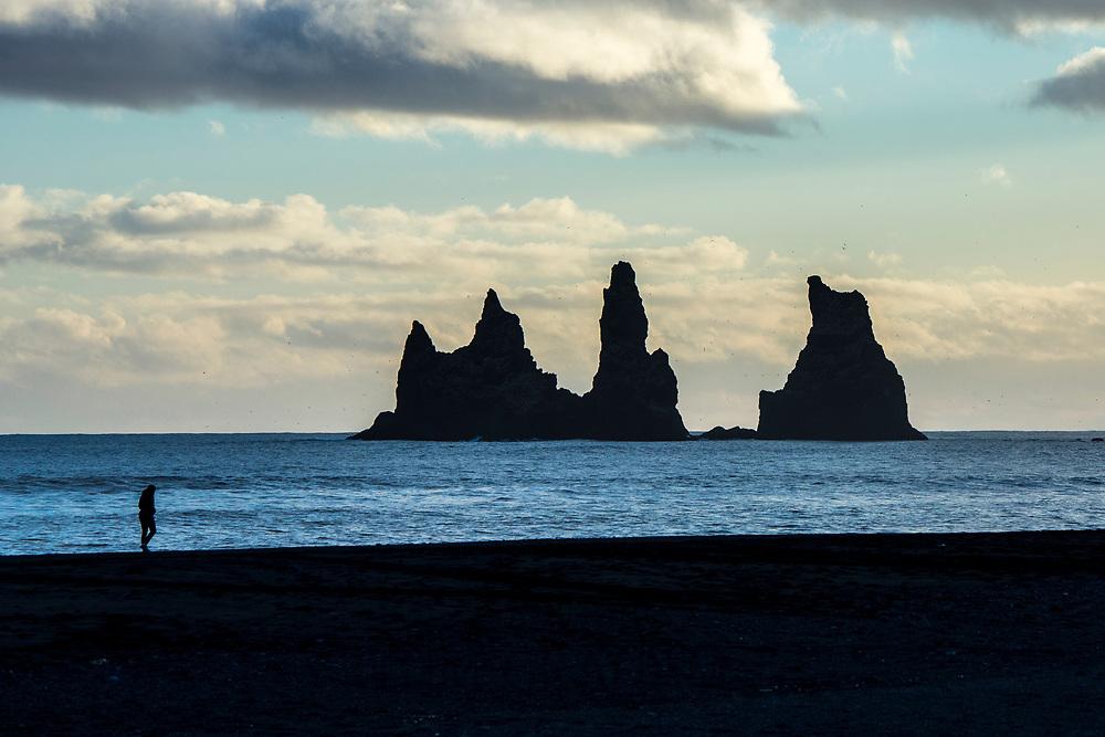 Tourist by Reynisdrangar basalt sea stacks (troll rocks) and black volcanic sand beach Reynisfjara near the village Vík i Myrdal, South Iceland