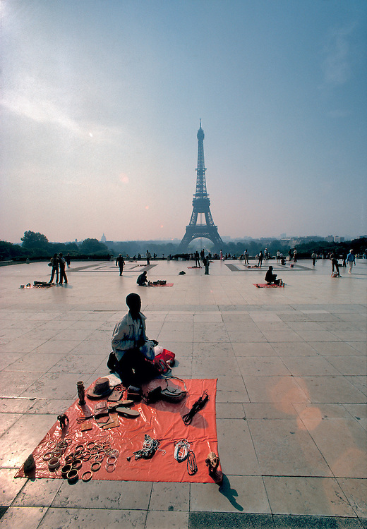 A street vendor displays his wares on the terrace near the Eiffel Tower in Paris, France.