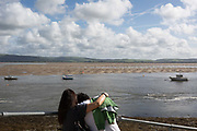 A couple hug while looking out across the estuary of the River Dovey at low-tide, on 12th September 2018, in Aberdovey, Gwynedd, Wales.