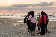 A group of women pray on the beach at sunrise on Hilton Head Island, SC
