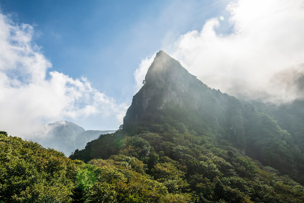 Hallasan National Park, South Korea - September 16, 2019: View from the Gwaneumsa Trail of a pointed mountain peak in Hallasan National Park. Located on Jeju Island, Hallasan National Park is home to South Korea's high mountain, called Hallasan (not pictured).