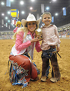 Child Sheep Racing<br /> <br /> Mutton busting is an event held at rodeos similar to bull riding or bronc riding, in which children ride or race sheep<br /> In the event, a sheep is held still, either in a small chute or by an adult handler while a child is placed on top in a riding position. Once the child is seated atop the sheep, the sheep is released and usually starts to run in an attempt to get the child off. Often small prizes or ribbons are given out to the children who can stay on the longest. There are no set rules for mutton busting,<br /> The vast majority of children participating in the event fall off in less than 8 seconds. Age, height and weight restrictions on participants generally prevent injuries to the sheep, and implements such as spurs are banned from use. In most cases, children are required to wear helmets and parents are often asked to sign waivers to protect the rodeo from legal action in that event.<br /> <br /> Photo shows: Amarillo, Texas, USA - Rosanna Pace, Miss Rodeo Texas, presents mutton busting trophy to Kason Proffitt, 5, at the finals of the Tri-State Fair and Rodeo in Amarillo, Texas.<br /> ©Exclusivepix