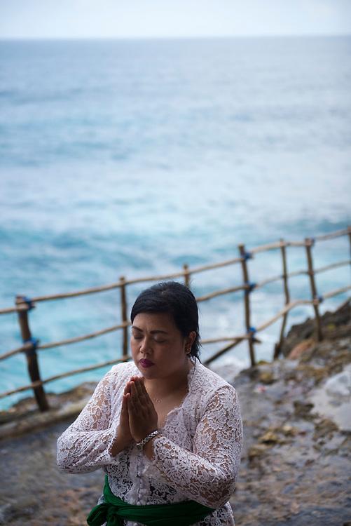 Nusa Penida, Indonesia - September 30, 2017: A Balinese woman prays at a small seaside temple at Peguyangan Waterfall on Nusa Penida, an island located off the coast of Bali.