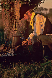 man cooking at the campfire