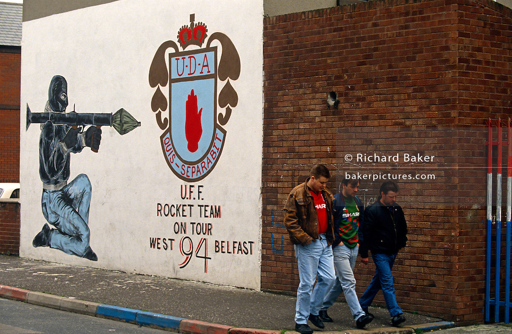 With hands in their pockets and walking in step, three friends pass along a street off the Shankhill Road in Belfast, Northern Ireland, have just passed beneath a Loyalist mural drawn by a paramilitary artist, whose handiwork is based on a well-known representation of a kneeling gunman shouldering a rocket-propelled grenade (RPG) and aiming past the crest of the protestant Ulster Defence Association (UDA), the organisation behind many a sectarian action against neighbouring catholic supporters of the Irish republican Army (IRA). In loyalist areas, the red, white and blue of the British Union Jack is painted on kerbs, houses and railings to signify peoples' allegiance to the crown, having historically followed the 17th century activities of King William of Orange against Catholics.   .