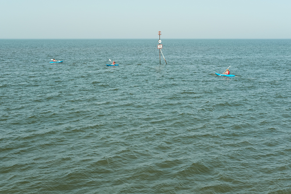 Kayaks passing the end of a groyne enjoying the last hot day of the Summer in Hunstanton Norfolk, the first summer in the UK during the COVID-19 pandemic.<br /> Many visitors to Hunstanton hire Kayaks from the North Promenade to paddle in the the Wash/North Sea<br /> <br /> Photo by Jonathan J Fussell, COPYRIGHT 2020