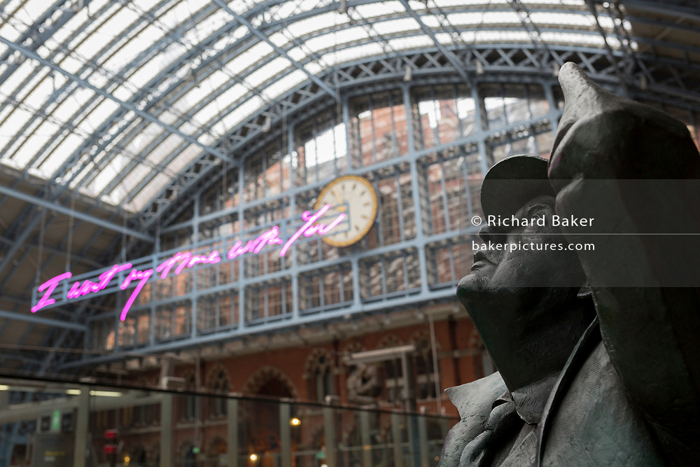 """The statue of poet John Betjeman by Martin Jennings looks up to the new artwork entitled 'I Want My Time With You' by British (Britpop) artist Tracy Emin which hangs over the main concourse at St. Pancras Station, on 10th April 2018, in London, England. In the sixth year of the Terrace Wires Commission - and in celebration of the 150th anniversary of St Pancras International and the 250th anniversary of the Royal Academy of Arts, at one of London's mainline station, the London hub for Eurostar - the 20 metre-long greeting to commuters reads 'I Want My Time With You' and Emin thinks that arriving by train and being met by a lover as they put their arms around them, is very romantic."""" The Brexit-opposing artist also said she wanted to make """"a statement that reaches out to everybody from Europe arriving in to London""""."""