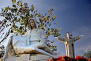 """Statue of Mary with Christ taken down from the cross, with """"Christ of Vung Tau"""" in background. """"Christ of Vung Tau"""" is a statue of Jesus standing on Nui Nho (Tao Phung, or Little Mountain), in Vung Tau. Built between 1974 and 1993, it is 32 metres (105 ft) high, standing on a 4 metre (13 ft) high platform, for a 36 metre (118 ft) total monument height, with two outstretched arms spanning 18.3 metres (60 ft). There is a 133-step staircase inside the statue leading to observation points on both shoulders. Vung Tau, Vietnam"""