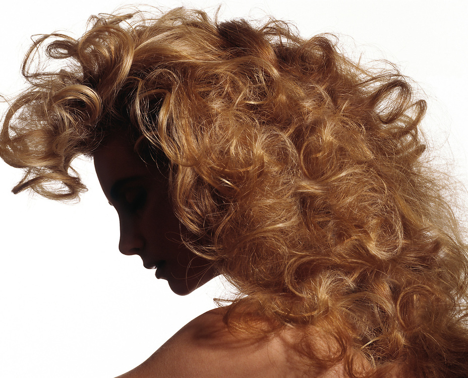 Woman's face in silhouette with long blond wavy hair. Cropped below shoulders with a white background